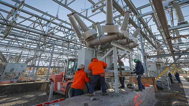 men working on electric unit