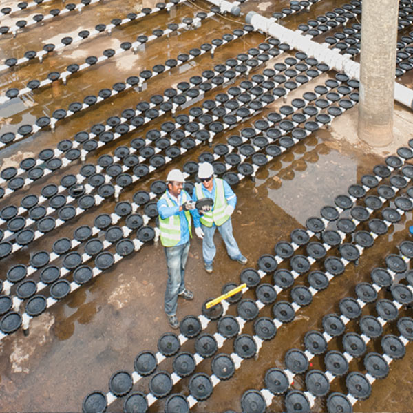 two workers looking at water supply materials